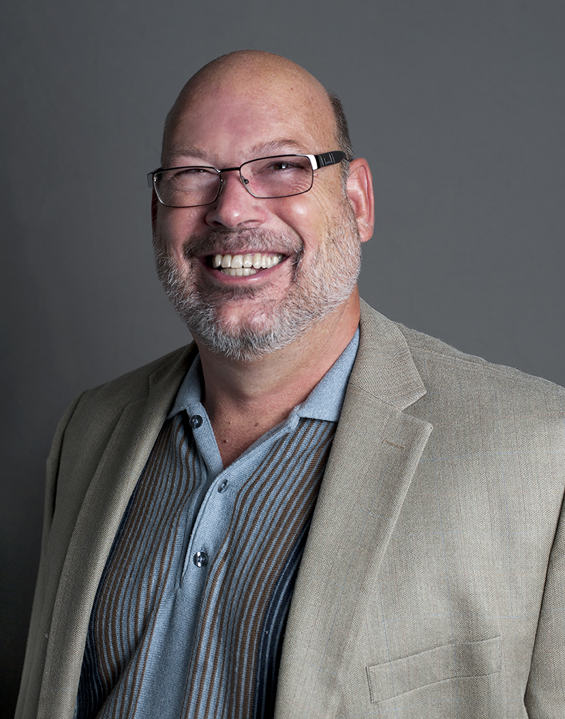 Headshot of a Caucasian smiling man with glasses in a polo shirt and beige suit jacket, in front of a gray background.