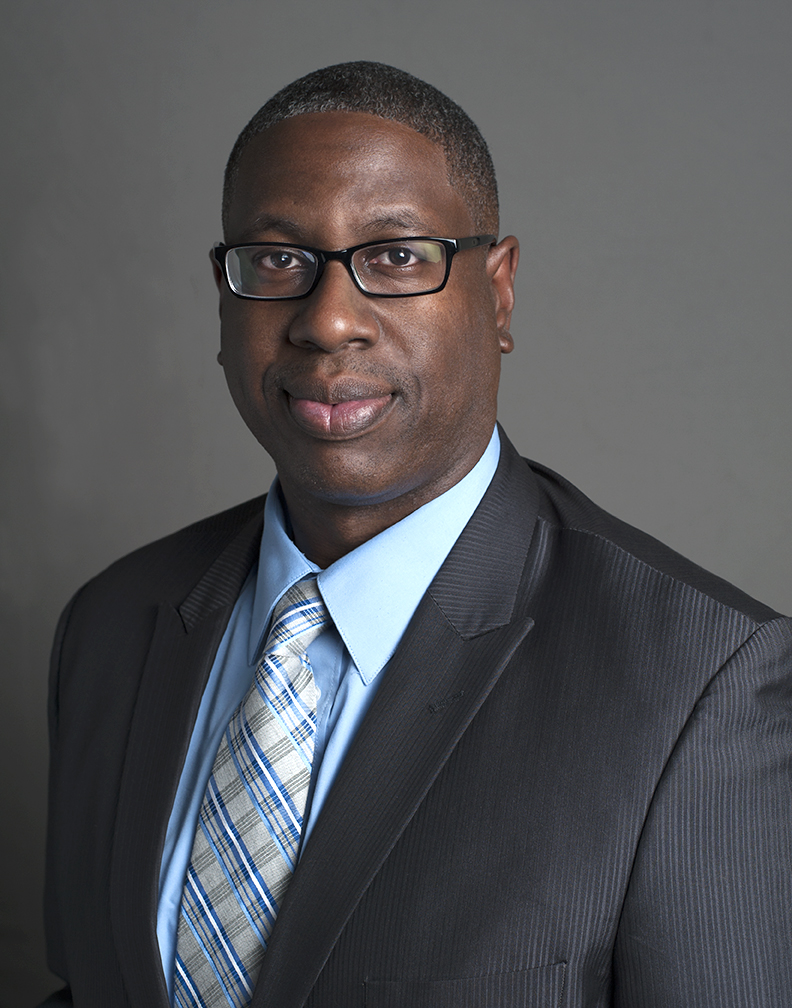 Headshot of an African American man in glasses, in a suit and tie, in front of a gray background.