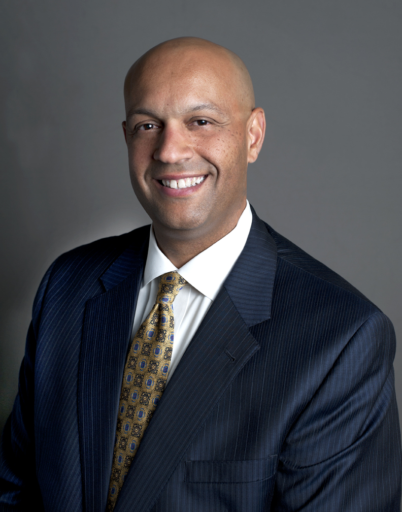 Headshot of an African American smiling man in a dark blue suit and yellow patterned tie, in front of a gray background.