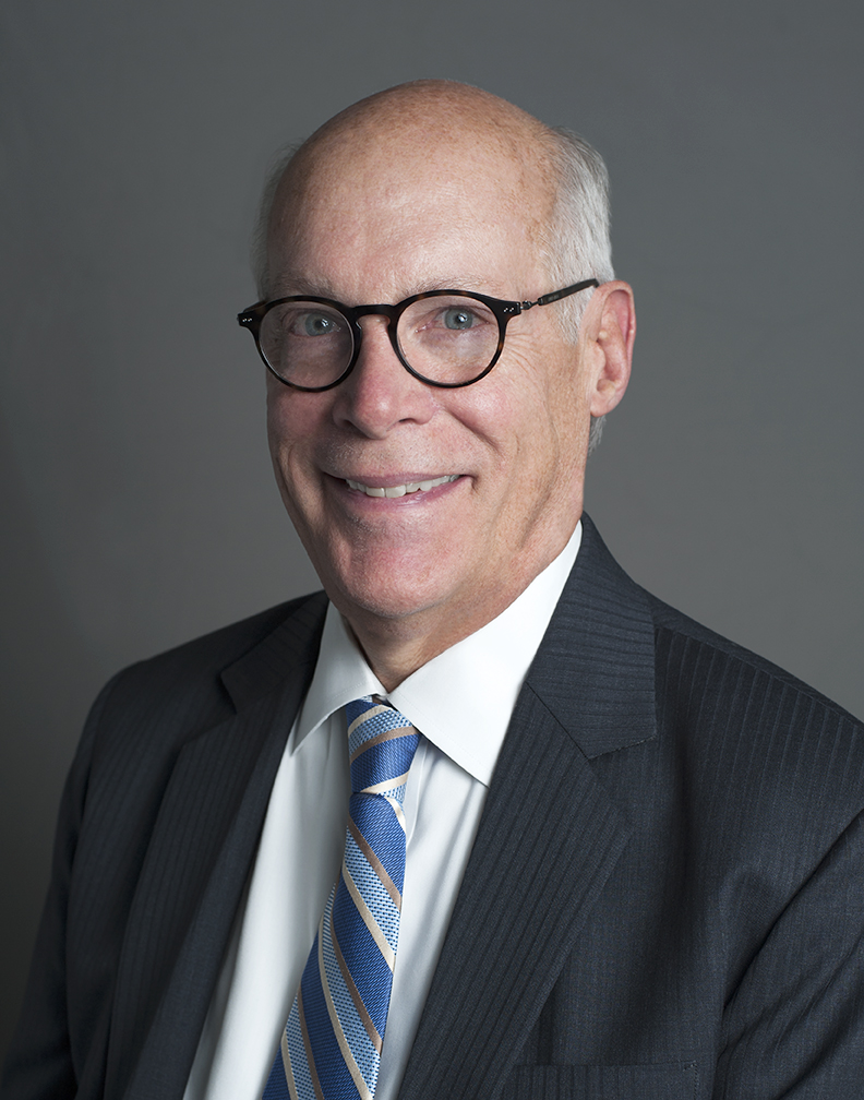 Headshot of a Caucasian smiling man in glasses wearing a dark suit and blue striped tie, in front of a gray background.