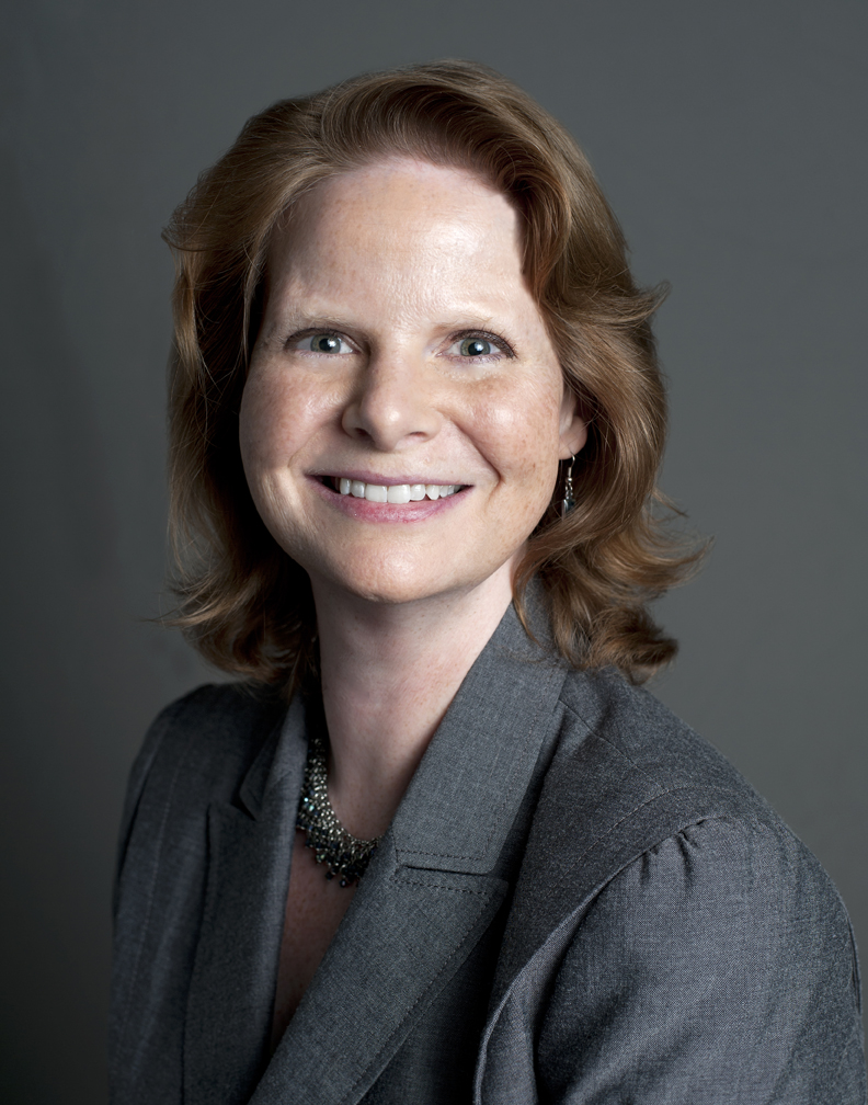 Head shot of a Caucasian woman in gray suit against a gray background.