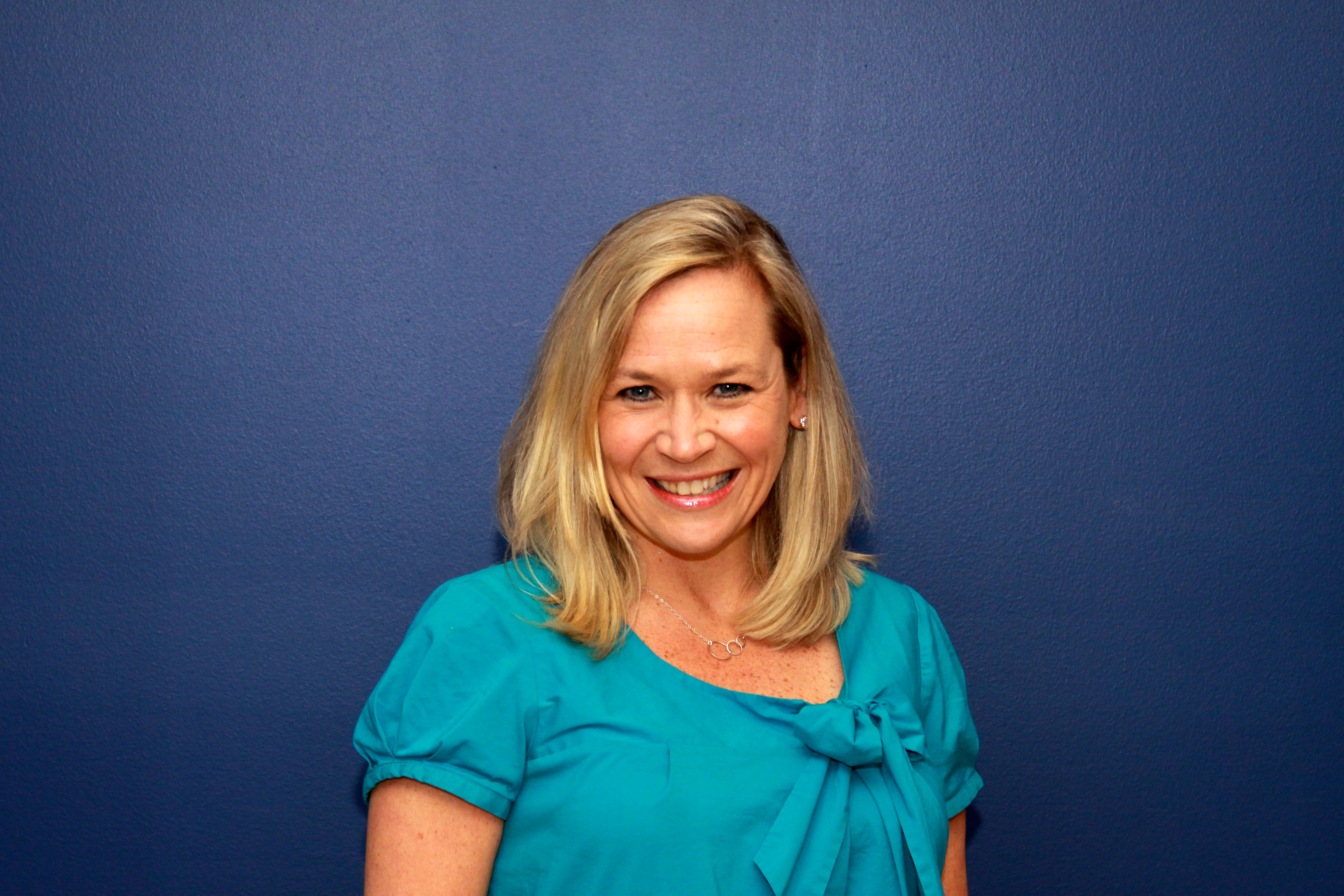 A smiling woman in a light blue top against a dark blue background.