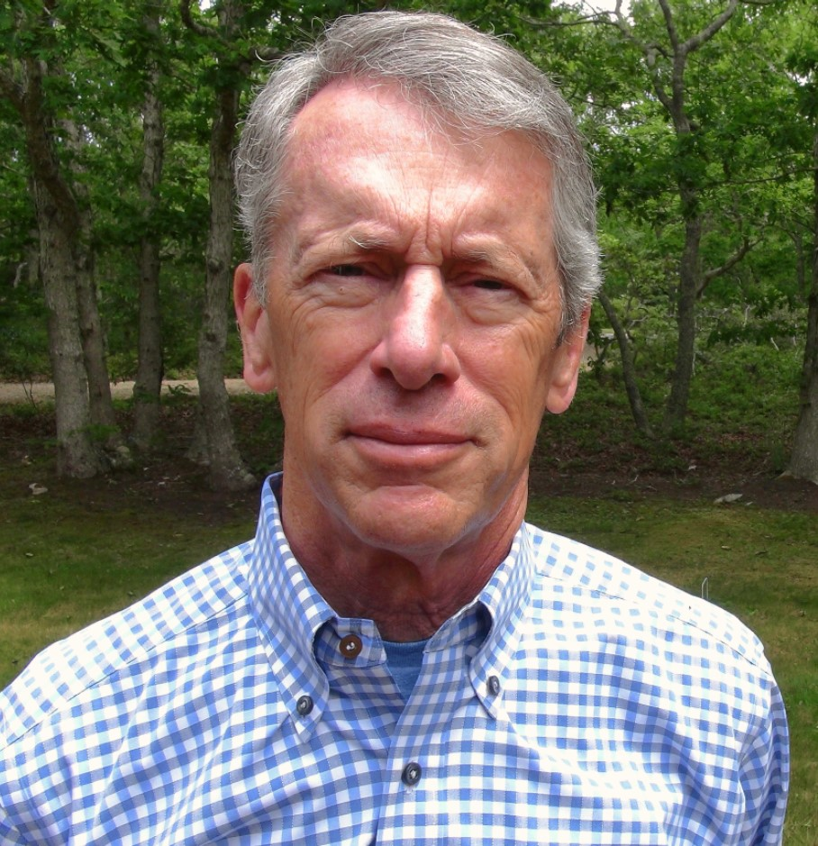 Heashot of a Caucasian man in a blue checked shirt, in front of green grass and trees.