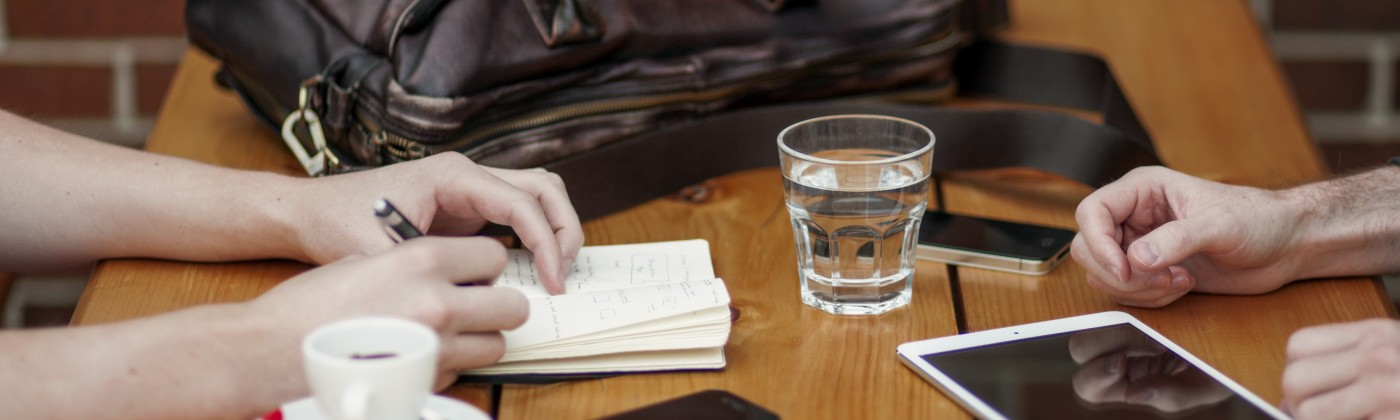 Two sets of hands, facing one another on top of a wooden table. Surrounded by personal electronics, a glass of water, espresso and briefcase. One hand is writing in a notebook.