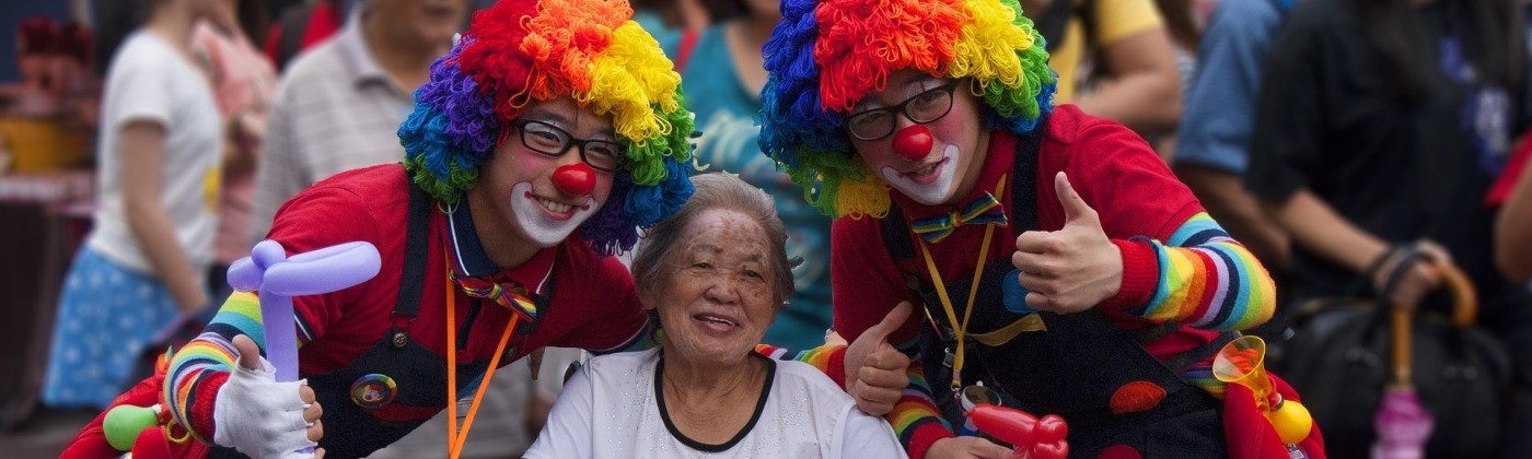 A smiling elderly woman in a wheelchair with two people dressed as clowns on either side