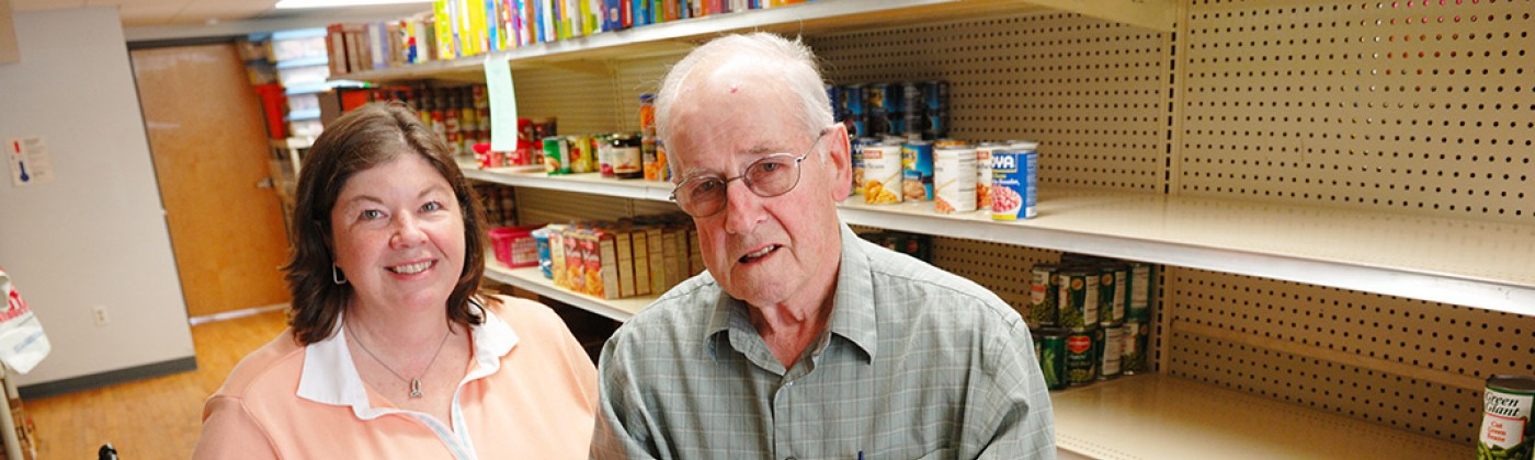 A man and woman working in a food pantry.