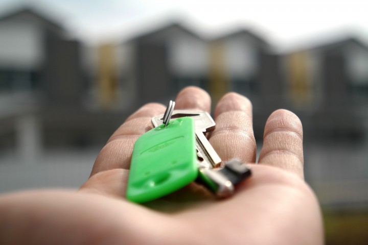 A hand holding out a set of keys on a green keychain