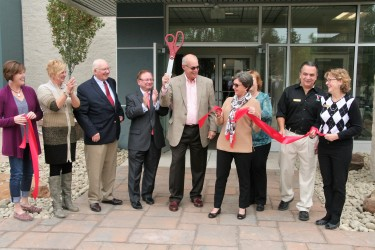 A line of people celebrating a ribbon cutting ceremony.