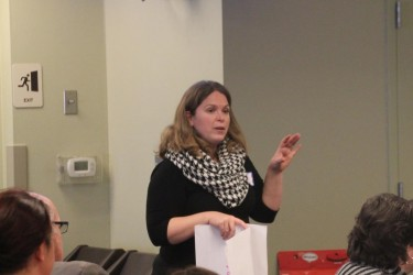 A woman in a graphic scarf, standing in front of people making a presentation.