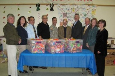 A line of people stand behind a table with three large plastic bins full of candy.