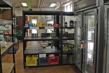 Shelves and glass-fronted refrigerators in a food pantry.