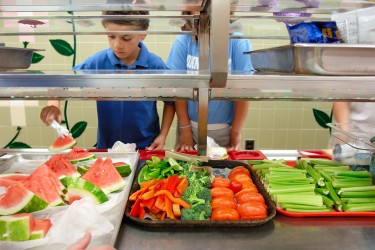 Children selecting fresh produce in a cafeteria line.
