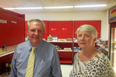 Two people in front of food pantry shelves.
