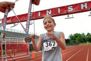 A girl accepts a medal for finishing a foot race.
