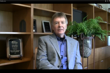 A man in a suit jacket, sitting in front of wood bookshelves and a fern.