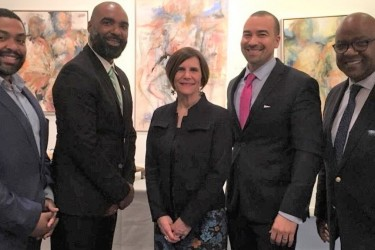 Four men of color and one Caucasian woman, all in suits, posing for a picture.