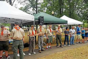 A line of boy scouts in front of tents.
