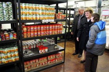 Three people looking at fully stocked food pantry shelves.