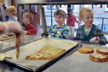 Kids in a cafeteria line getting pizza.