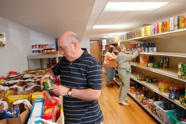 Three people stocking a food pantry's shelves.