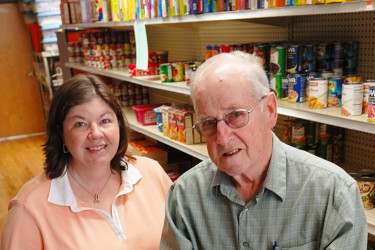 Two people in front of food pantry shelves, one is holding a cardboard box full of fresh vegetables.
