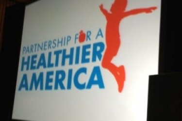 "Projection screen that displays a silhouette of a child jumping with the words, ""Partnership for a Healthier America."""