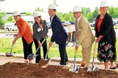 Five people with shovels participating in a groundbreaking ceremony.