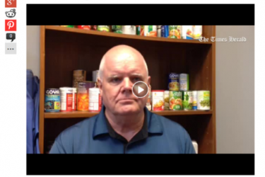 Still of a video of a Caucasian man in front of shelves with canned goods.