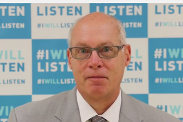 "Head shot of a man in front of a background of repeating tiles that read, ""I will listen."""