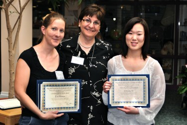 Three women posing for the camera, two hold up certificates.