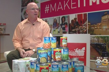 A Caucasian man sitting behind canned food.
