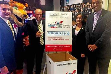 Four people and a person in a mascot costume, standing by a box for food donations.