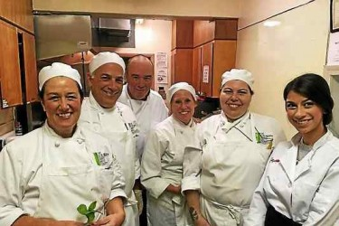 A line of chefs smiling and posing for the camera.